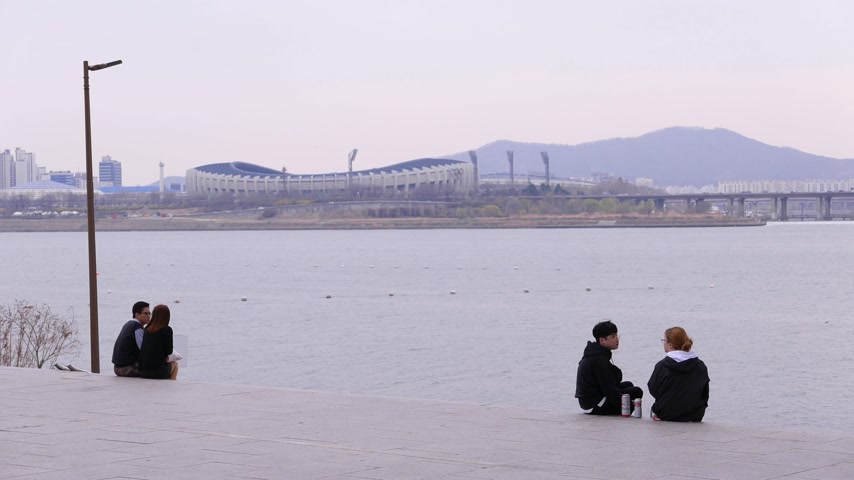 han river : Young korean couple sitting on river Han embankment Seoul, South Korea