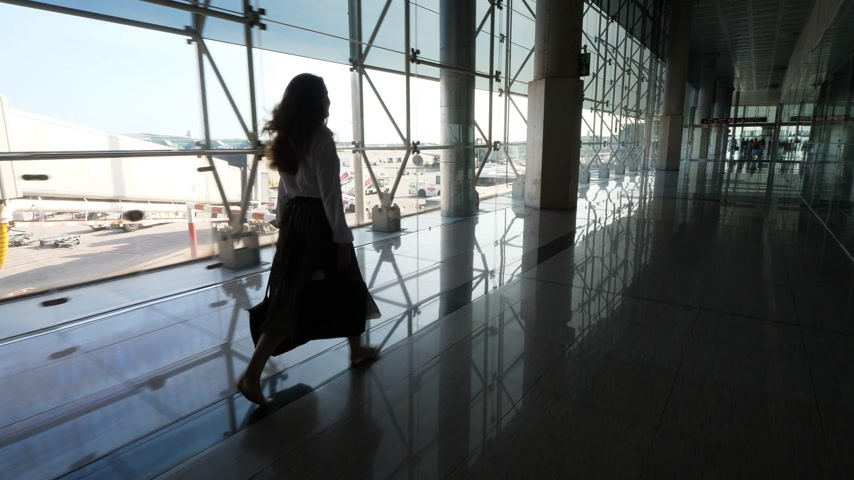 proceed : Tourist girl walk in airport terminal against glass window with panorama on airplanes