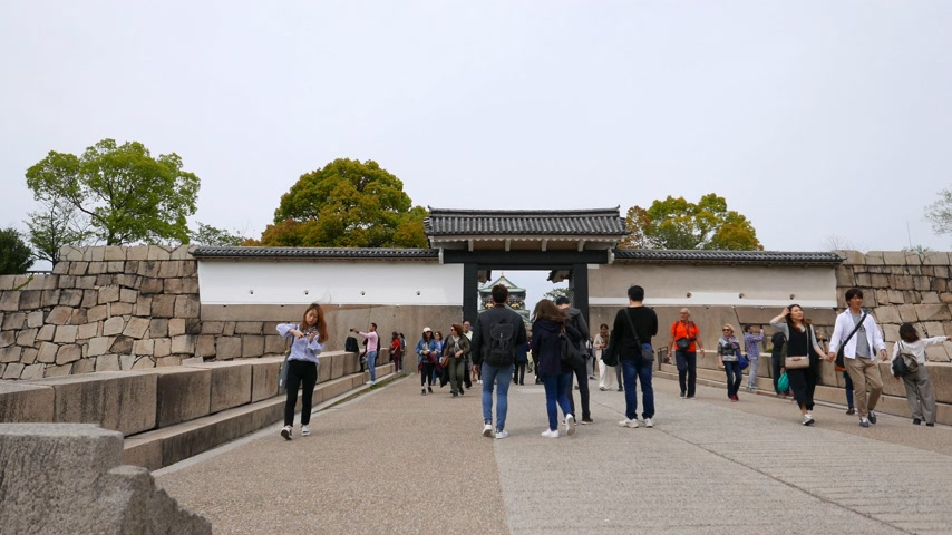 Young Japanese people walk from Osaka Castle through otemon western gate, Japen