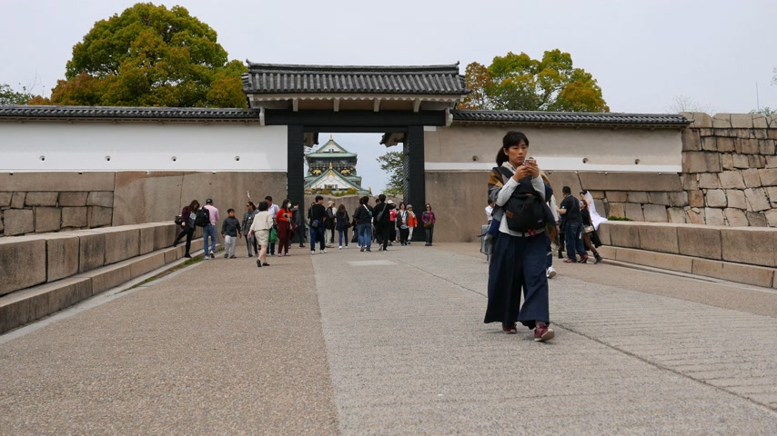 Asian tourist woman using smartphone go out from Osaka Castle western gate Stok Video