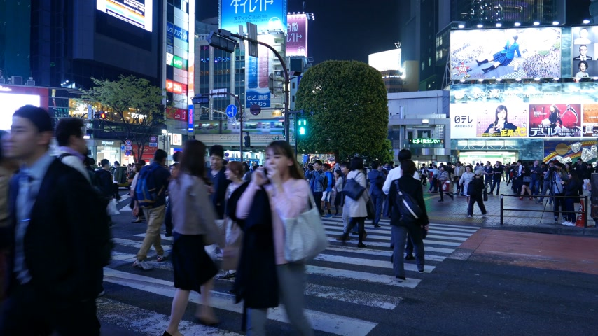 People walk on Shibuya crossroad. Bright neon light, train pass by, Tokyo, Japan Stok Video