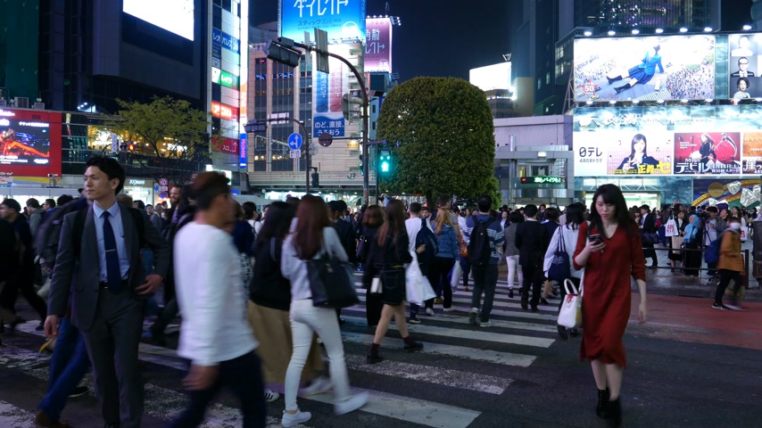 Bright lights at busy Shibuya intersection, many asian people cross road, Tokyo