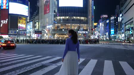 Tourist girl standing at Shibuya road intersection at night, Tokyo, Japan Stok Video
