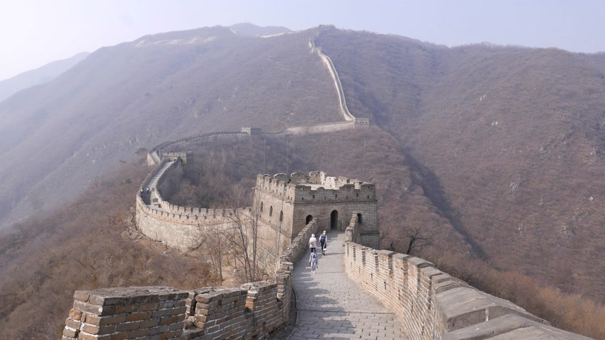 Tourists walk on winding road on Great Wall of China