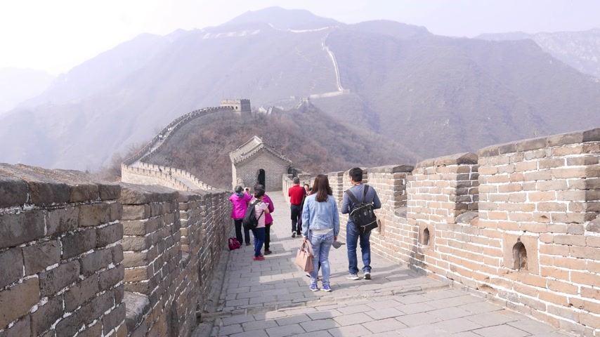 Asian tourists walk down on Great Wall of China