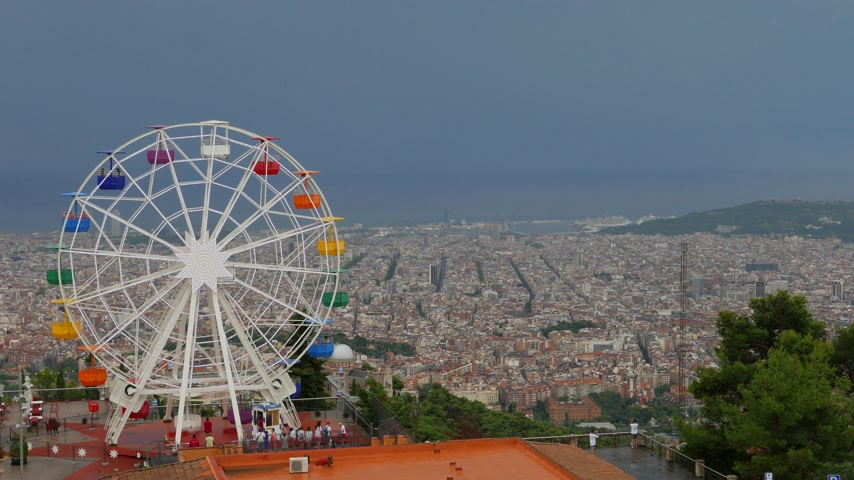 Ferris Wheel against gray sky and beautiful Barcelona panorama