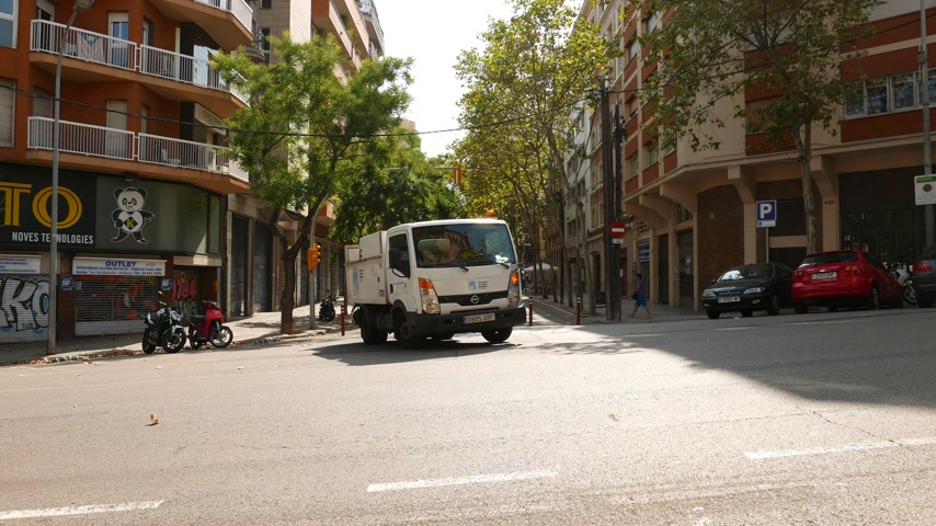 Little truck turning on T-junction on cosy Barcelona street