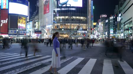 Time Lapse Tourist girl standing at Shibuya crossing at night, Tokyo, Japan