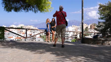 Man taking photos tourist girls on viewing point, Crete, Agios Nikolaos