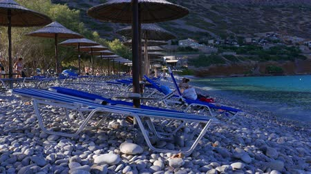 Sun beds and umbrellas on gravel beach, Crete