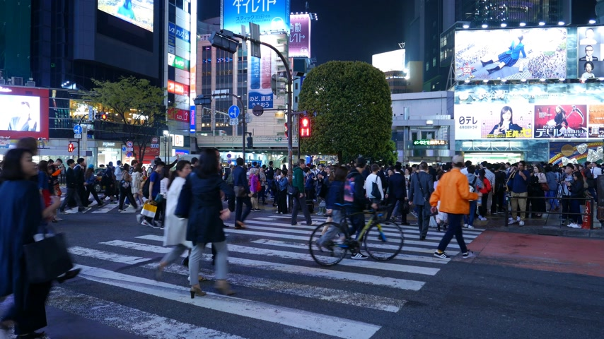 People cross road at famous Shibuya conjunction at night, Tokyo, Japan Stock Footage