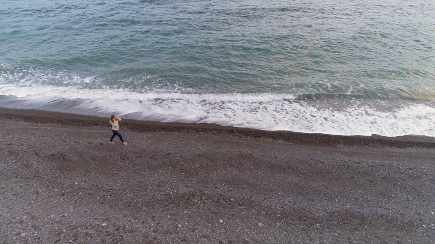 pursue : Young Woman is Walking on Sea Shore with Splashing Waves. Aerial View. Drone is Following Model and Flying Around
