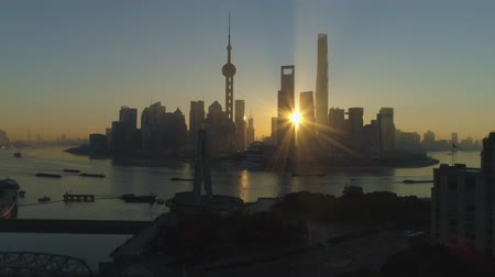 huangpu river : Panoramic Shanghai Skyline at Sunrise. Lujiazui Financial District and Huangpu River. China. Aerial View. Drone is Flying Upward and Sideways. Establishing Shot Stock Footage