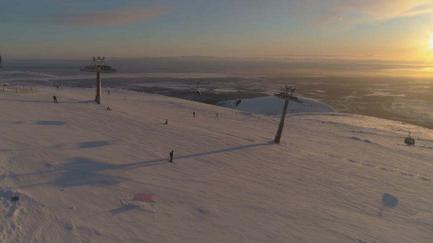 pursue : People are Skiing and Snowboarding on Ski Slope with Cable Car at Sunny Winter Sunset. Aerial View. Drone is Flying Sideways. Establishing Shot Stock Footage