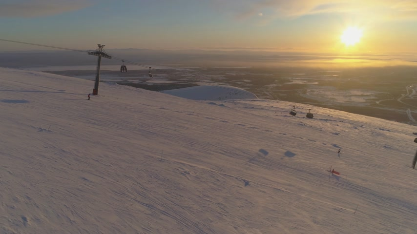 pursue : People are Skiing and Snowboarding on Ski Slope with Cable Car at Sunny Winter Sunset. Sun in Frame. Aerial View. Drone is Flying Sideways. Establishing Shot