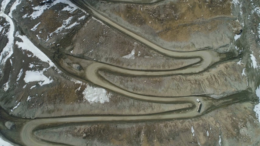 Тибет : Trucks Go on High Mountain Road Pass. Aerial Vertical Top-Down View. Drone is Flying Upward. Establishing Shot