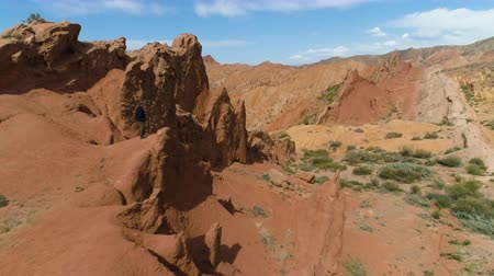 kumul : Tourist Man Takes Picture of Red Canyon and Blue Sky at Sunny Day. Aerial View. Drone Orbits Around, Camera Tilts Down. Establishing Shot