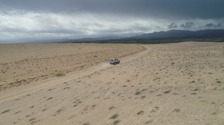 low angle shot : Suv Car Goes on Sandy Wasteland. Desert Landscape and Stormy Clouds. Aerial Low Angle View. Drone is Flying Sideways and Distancing From Car Stock Footage