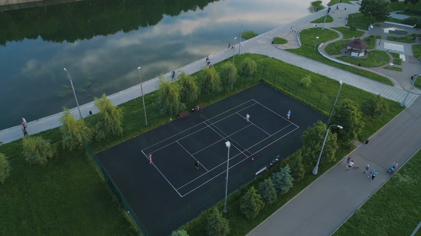 теннис : Flying over players playing tennis on a court in green city park. People are walking on sidewalk. Camera is tilting down. Aerial view