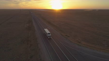 tilt down : Truck is going on highway in the sunny evening. Aerial view. Camera is tilting down Stock Footage