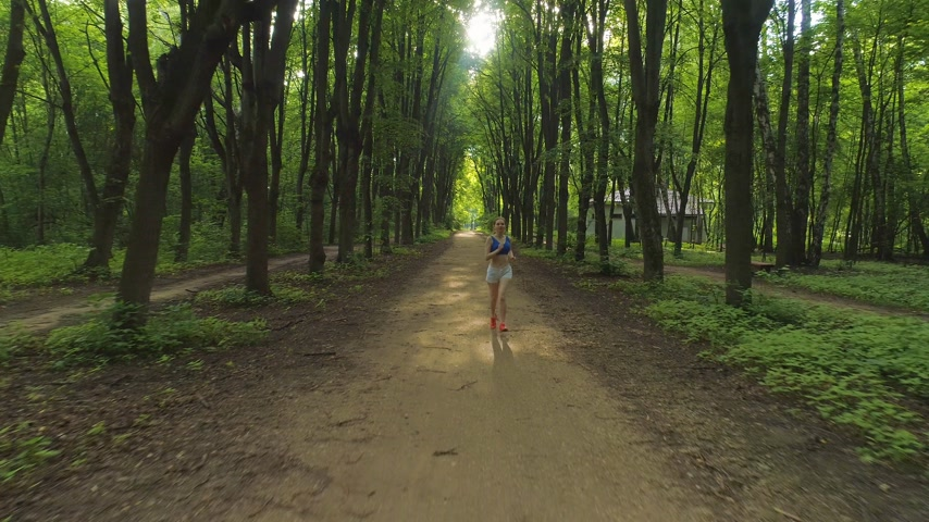назад : Young healthy woman is running in beautiful green alley in the sunny morning. Drone is flying backward and upward. Aerial view.