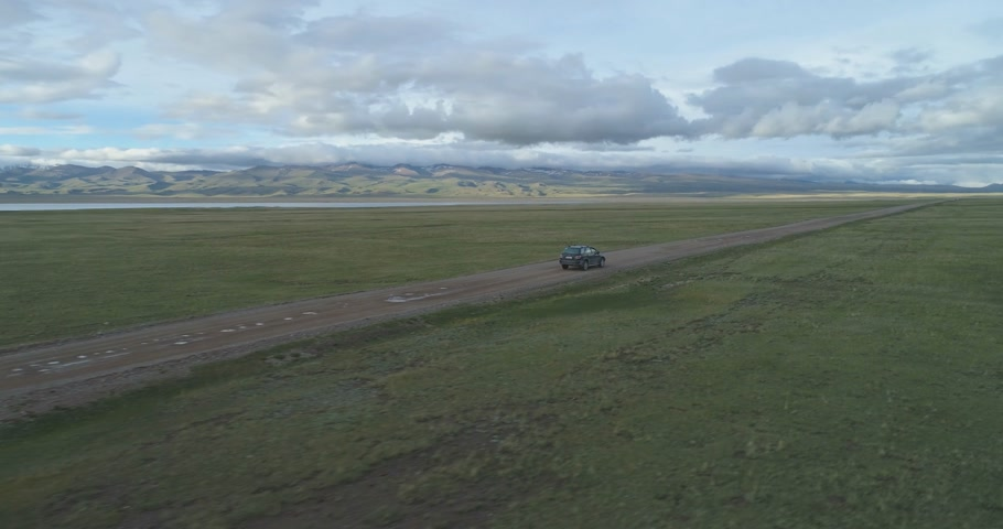 çakıl : Suv Car Goes on Gravel Road in Summer Day. Mountains and Lake Shore on Background. Aerial View. Drone is Orbiting around. Establishing Shot