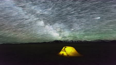 halmozott : Cumulative Time Lapse Of Night Starry Sky with Star Trails over Yellow Glowing Tent