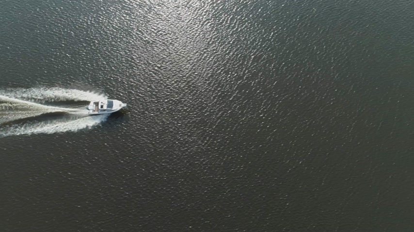 oldalt : Luxury Speed Motor Boat in the Sea at Sunny Day. Aerial Vertical Top-Down View. Drone is Flying Sideways to the Right Stock mozgókép