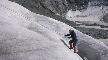 ascenso : Mountaineer Man in Crampons utiliza Jumar en Fixed Rope para ascender en Mountain at Sunny Day. Camara lenta Archivo de Video