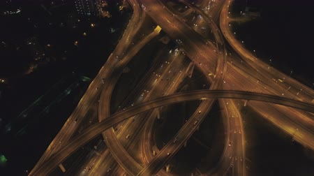 назад : Illuminated Complex Road Intersection and Cars Traffic at Night. Drone is Flying Backward, Camera is Tilting Up. Aerial Vertical View