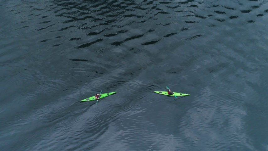 каноэ : Two Green Kayaks in Turquoise Water of the Geiranger Fjord. Norway. Aerial Vertical Top-Down View. Drone is Flying Sideways