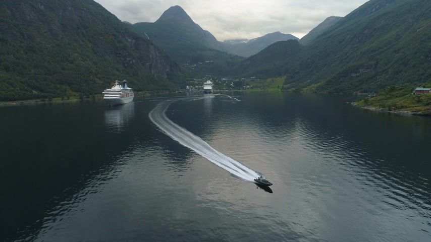 назад : Small Motor Speed Boat and Large Cruise Liner in Geiranger Fjord in Summer Day. Norway. Aerial View. Drone is Flying Backward, Camera is Tilting Down