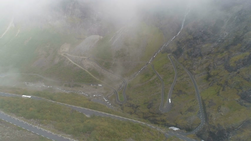 serpentine : Trollstigen - Famous Trolls Path in Norway. Curved Mountain Road in Fog. Aerial View. Reveal Shot. Drone is Flying in Mist