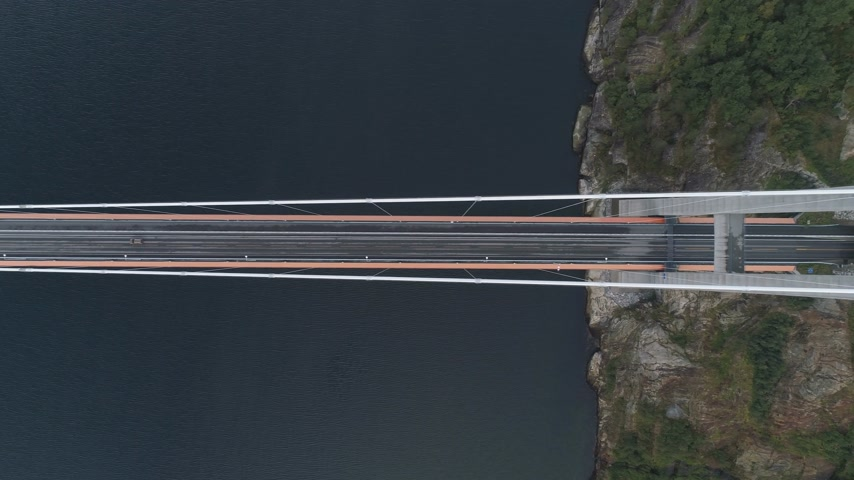 oldalt : Hardanger Suspension Bridge across the Hardangerfjord with Passing Car in Norway. Aerial Vertical Top-Down View. Drone is Flying Sideways