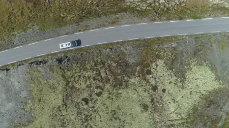 oldalt : White Motorhome Car is Going on Mountain Road in Norway at Summer Sunny Day. Aerial Vertical Top-Down View. Drone is Flying Sideways