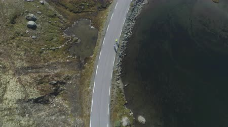 tilt down : Professional Cyclists in Helmets are Biking on Mountain Road in Norway at Summer Sunny Day. Aerial Vertical Top-Down View. Drone is Flying Forward Stock Footage