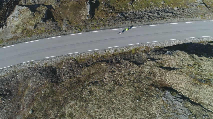 tilt down : Cyclists in Helmets are Racing on Mountain Road in Norway at Sunny Summer Day. Aerial Vertical Top-Down View. Drone is Flying Sideways
