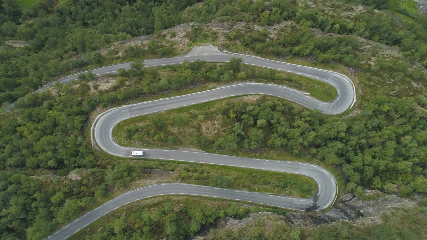 downwards : White Motorhome Car is Going on Winding Road in Norway. Green Forest. Aerial Vertical Top-Down View. Drone is Flying Downwards