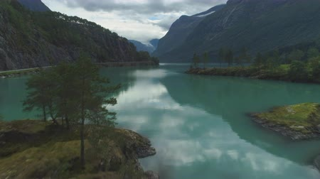 flying upwards : Lovatnet Lake with Turquoise Water. Green Islands and Mountains in Summer Day. Norway. Aerial View. Drone is Flying Forward and Upward