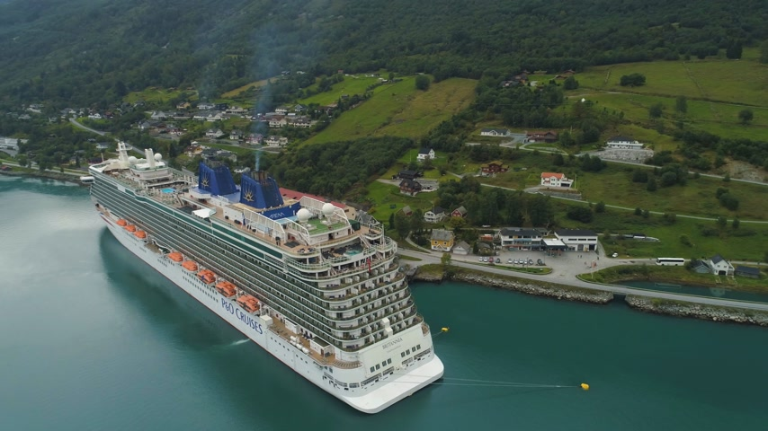 ancorado : OLDEN, NORWAY - SEPTEMBER 6, 2018: Large Luxury Cruise Liner is Moored in Town. Fjord of Norway. Aerial View. Drone is Orbiting Around and Ascending, Camera Tilts Down