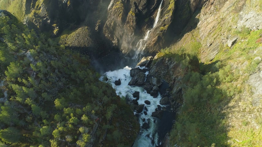 tilt down : Voringfossen Waterfall and Cliffs with Green Trees in Norway at Sunny Summer Day. Aerial Vertical Top-Down View. Drone is Flying Forward, Camera is Tilting Down