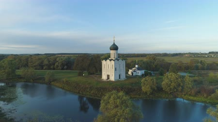 ascend : Church of the Intercession on the Nerl River at Sunny Evening. Vladimir Region, Russia. Aerial View. Drone is Orbiting Around Stock Footage
