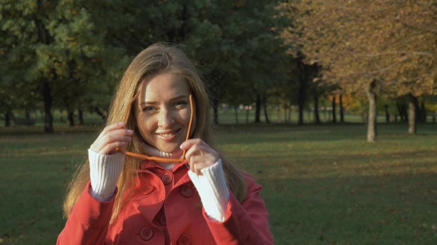 handheld shot : Young Smiling Woman Wears on Glasses in Green Park. Medium Shot. Slow Motion Stock Footage