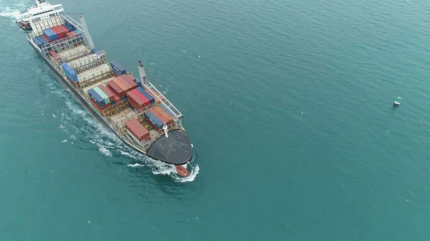 tilt : Cargo Ship in the Sea. Aerial View. Camera Tilts Down
