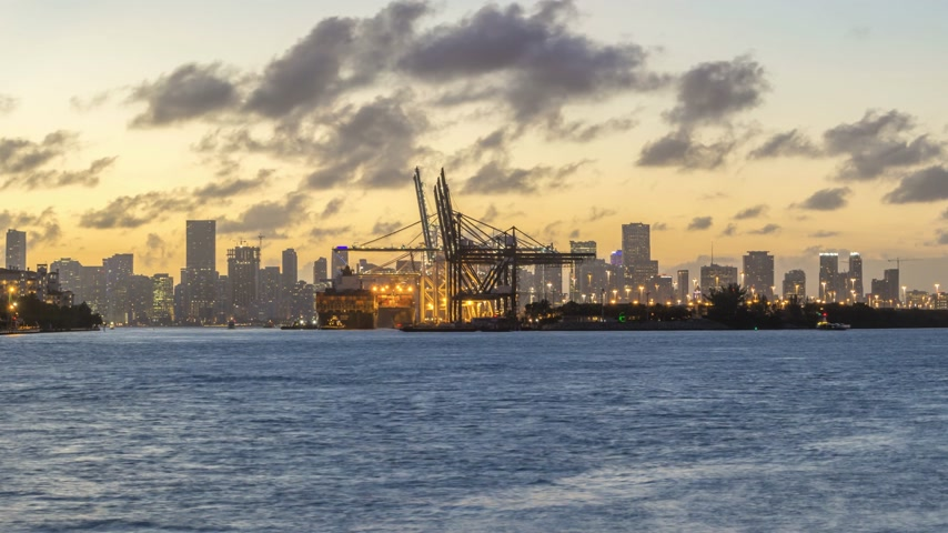 containerschip : Miami Port en Miami Urban Skyline in avond. Time Lapse. In zoomen Stockvideo