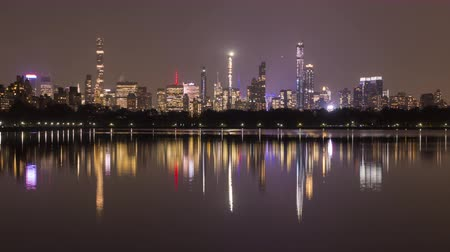 reservoir : Manhattan Skyline and Reflection in Lake in Central Park at Night. New York City. United States of America. Time Lapse. Zoom In