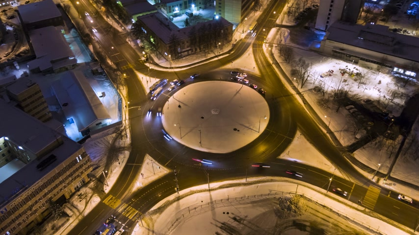 hyper : Illuminated Traffic Circle in the City and Cars at Winter Night. Round Crossroads. Aerial Vertical Top-Down View. Drone Hyper Lapse. Orbiting Stock Footage