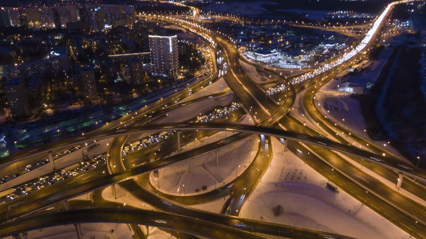 passagem elevada : Illuminated Complex Road Junction and Cars Traffic at Winter Night. Drone is Ascending, Camera Tilts Down. Aerial Time Lapse in Motion. Drone Hyper Lapse Vídeos