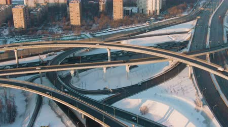 downwards : Complex Flyover and Road Traffic at Sunny Winter Day. Aerial View. Drone is Orbiting and Flying Downwards, Camera Tilts Up. Medium Shot
