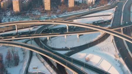 establishing shot : Complex Road Flyover and Junction, Cars Traffic at Sunny Winter Evening in City. Aerial View. Drone Flies Sideways. Medium Shot